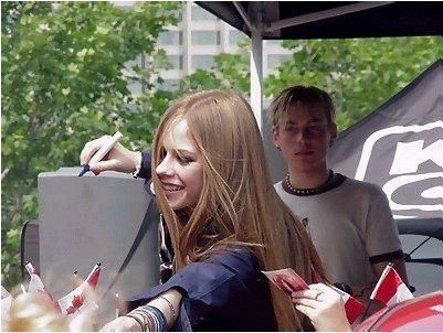 Really cool pic! Here is one of Avril giving an autograph. Evan is in the background :) Um I