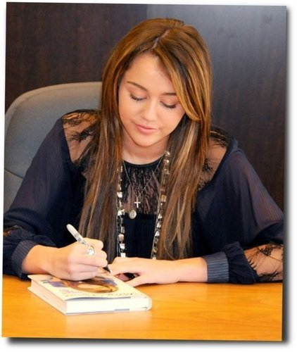 Miley autographing her biography