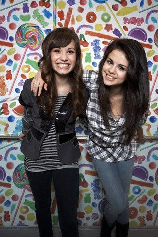 Selena Gomez and Demi Lovato wallpaper probably containing an outerwear, a well dressed person, and a hood titled Selena Gomez and Demi Lovato