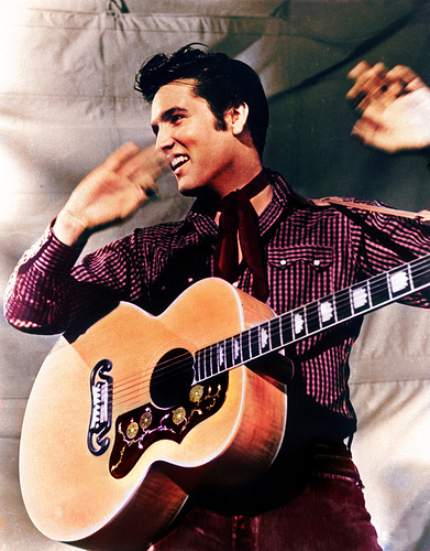 Elvis Presley wallpaper with an acoustic guitar, a snap brim hat, and a guitarist titled Elvis Presley 1957 Loving You Movie Guitar Shot