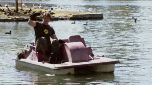 What does Captain Hammer mouth at Penny while he's operating the paddle boat?