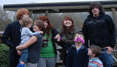 Rupert has one brother and three sisters. The big guy with black hair is James, the girl with green overhemd, shirt is Samantha, the girl pulling on her arm is Georgina and the other girl who's holding the baby is Charlotte. The three little boys are Rupert's cousins.