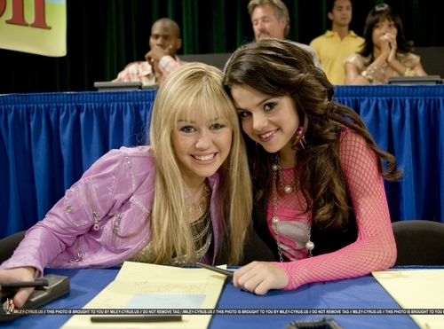 Miley Cyrus vs. Selena Gomez پیپر وال possibly with a sign, a reading room, and a newspaper entitled Miley and Selena are دوستوں forever :D
