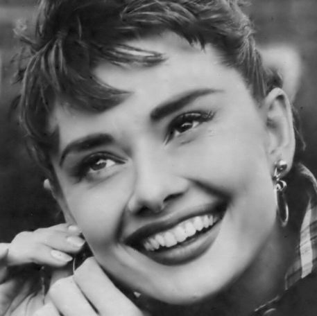 Audrey adjusting her earring on the set of Sabrina