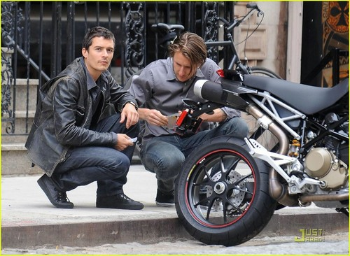 Orlando Bloom takes a look at his motorcycle's license plate