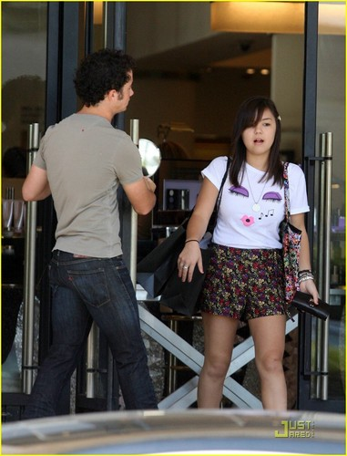 The Jonas Brothers wallpaper possibly with a street, a revolving door, and a sign entitled Kevin & Maya Out and About