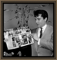 Elvis Holding A Magazine mostrando The Beatles