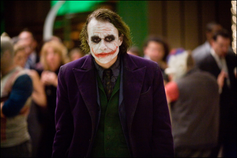 What two things does the Joker eat/drink when he invades Bruce Wayne's mansion during the party?