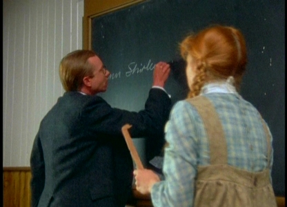 What does Mr. Phillips have Anne write on the blackboard after she hits Gilbert?