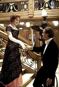 First couple who passes Jack and bows to him downstairs before dinner. What's the colour of woman's dress?