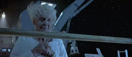 What Old Rose picks up from the table with things from Titanic's shipwreck?