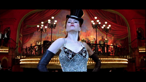 "What does Zidler's sign below the orchestra say when Satine is performing ""Sparkling Diamonds""? (The sign is behind Satine in the picture)"