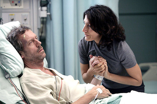 In what episode did Cuddy hold House's hand while at his bedside?