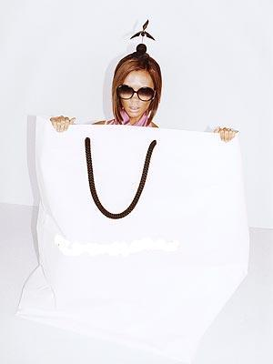 For which designer is she posing in this bag for?