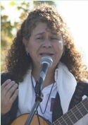 Maria Roza sings at the Oct. 25 Peace and Unity Rally at Sunnyview Park above photos of her two sons who were murdered in gang violence.